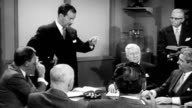 Men around meeting table having business meeting / one man standing and smoking cigarette pointing to others / men talking / men smoking cigars at...