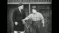 Fatty Arbuckle, Buster Keaton, and Al St John watch as Strongman (Charles A. Post) bullies woman (Molly Malone), and Arbuckle confronts the strongman, but is intimidated