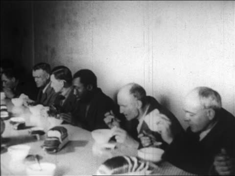 B/W 1929 men at table eating in soup kitchen / Great Depression / newsreel