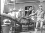 1923 WS Men attaching large oil hose to valve on tanker / United States