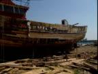 Men build a replica of Noah's Ark on a beach.