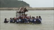 Men carry a mikoshi in the sea.