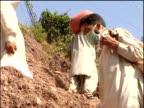 Men carry sacks of food aid up rocky hillside following earthquake Muzaffarabad Pakistan 16 Oct 05