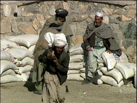 Men carry sacks of grain from aid stockpiles in refugee camp; Afghanistan Refugee Crisis 2001