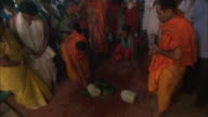 Men chops watermelon offering to Kali goddess with sword before placing it on shrine for Diwali Hindu Festival of Lights Available in HD.