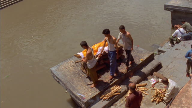 Men circle a body on a funeral pyre. Available in HD.