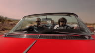 Men climb into a red vintage convertible and drive down a desert highway.