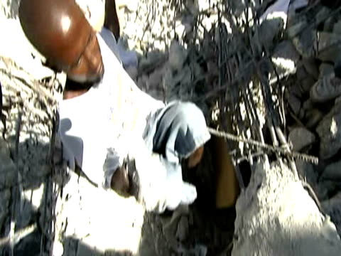 Men desperately remove rocks from rubble in search of relatives following devastating earthquake Haiti 14 January 2010