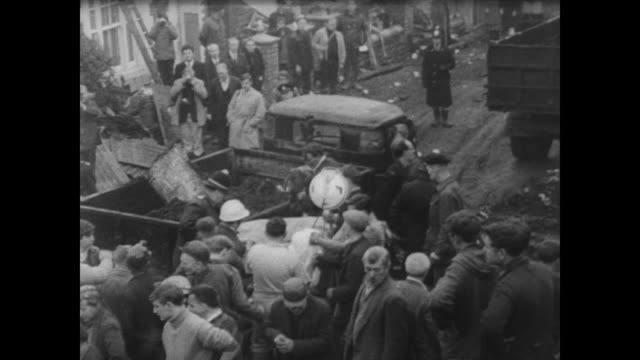 Men digging through rubble after avalanche of coal slag in the Welsh town of Aberfan / body removed on stretcher through packed village street /...