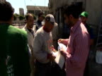 Men distribute leaflets on election day Syria