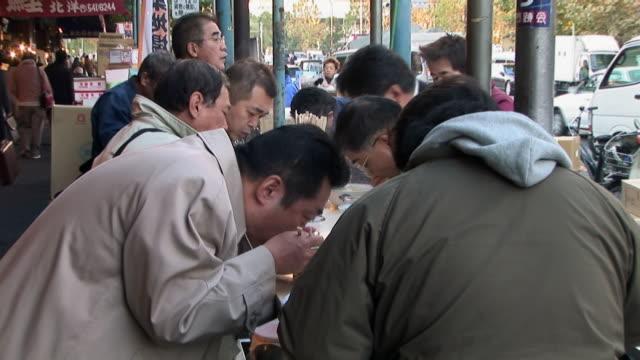 Men eating at noodle bar at Tsukiji fish market / Tokyo