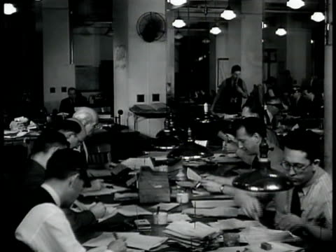 Men entering building sign 'New York Times' INT VS Men at tables w/ papers w/ pencil held by ear typing w/ headphones listening to radio Man typing...