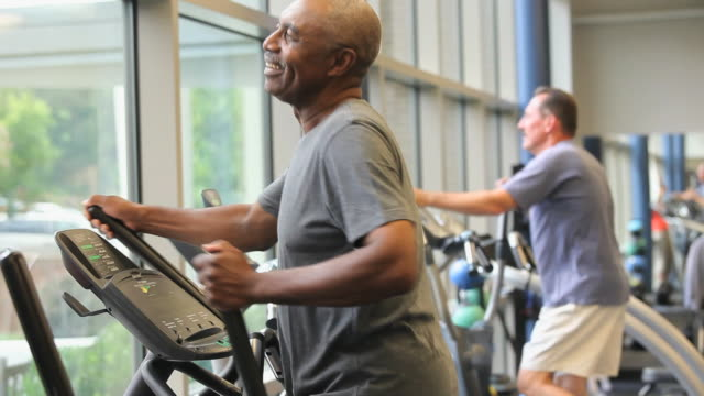 MS TU TD Men exercising on elliptical machine in gym / Richmond, Virginia, USA