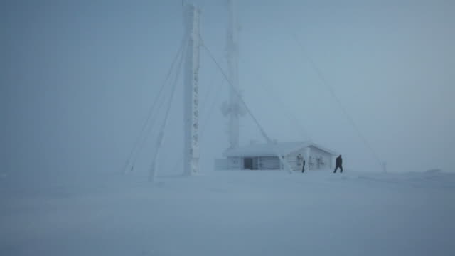 WS LS Men exiting monitoring station in snowy landscape / Finland
