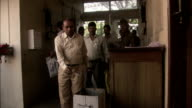 Men file along busy corridor in government offices placing paperwork in metal box Available in HD.