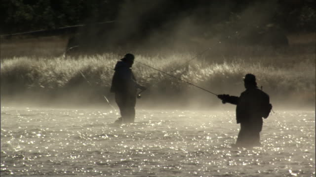 Men fly fishing in steaming river, Yellowstone, USA