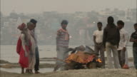 Men gather around a cremation fire in India.