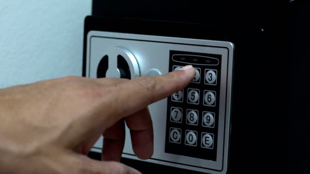 Men hands unlocking combination to safe in the hotel room