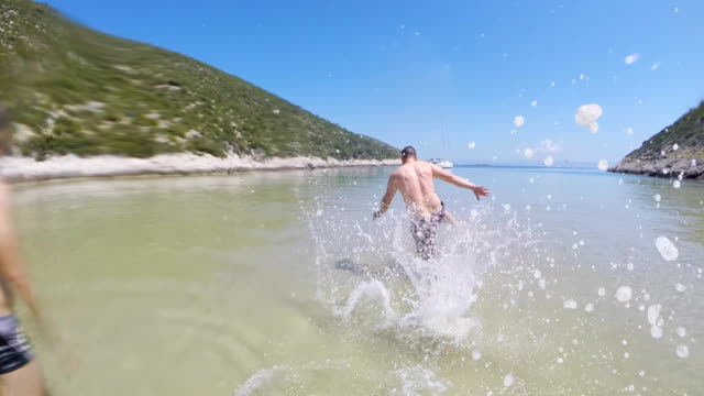 SLO MO Men Having Fun In Shallow Water