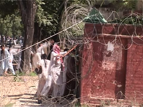 Men hit at barbed wire surrounding the Red Mosque complex and try to pull it during the attacks of July 2007