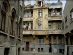 Men hoisting wardrobe on rope up side of building Bucharest