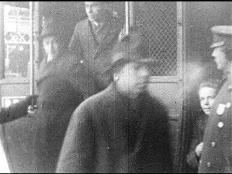Men in coats hats walking on city sidewalk MS Men in coats hats getting out of police wagon PAN INT Courtroom w/ jury taking seats DEPORTATION Women...