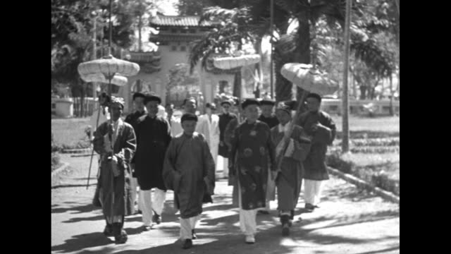 VS men in dark aodai and caps walking with others in white suits shaking hands / men walk along carrying paper parasols approaching elaborate gate /...