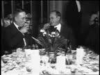 B/W 1916 PAN 2 men in formalwear sitting at round table in restaurant + toasting / newsreel