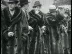 B/W 1936 men in fur coats + hats smoking + smiling / Rockefeller Center, NYC