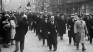 Men in military uniforms and plain clothes march through the streets of New York with crowds watching from the sidelines / marchers walk determinedly...