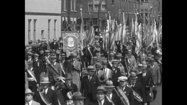 Men in military uniforms and two groups of women in uniforms marching in formation down street band behind them / women in uniforms marching down...