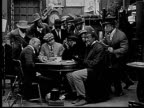 1916 B&W MS men in poker game hiding cards and chips after man enters and speaks to them/ man standing up and reading paper