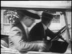 B/W 1925 2 men in straw hats drinking sneakily from flask in car / newsreel