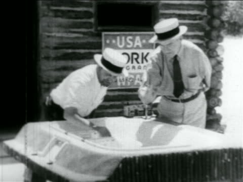 B/W 1934 2 men in straw hats looking at model of stadium in WPA construction project / documentary