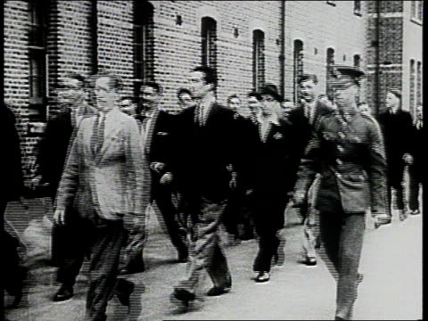 men in street clothes marching past camera / new recruits removing street clothes putting on uniforms