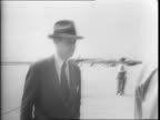 Men in suits gather near a plane while photographers move around them / Henry Ford speaks to William Averill Harriman / Edsel Ford talks with British...