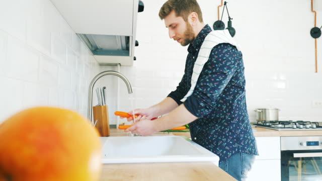 Men in the kitchen washing vegetables.