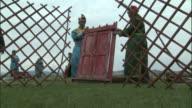 Men in traditional clothes erect wooden door in framework of ger, Bayanbulak grasslands.