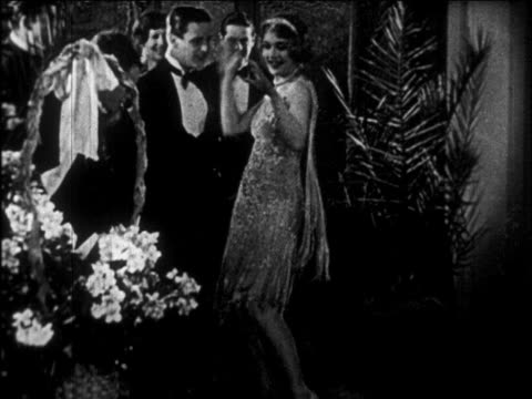 B/W 1926 men in tuxedos watching as woman in dress dances wildly at party / newsreel