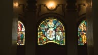 Men in white robes pass by a row of glowing stained glass windows inside a church. Available in HD.