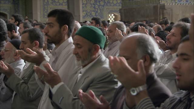 MS ZI Men kneeling during Friday prayers in Imam Mosque, Esfahan, Iran