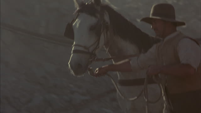 Men lead horses through a corral.