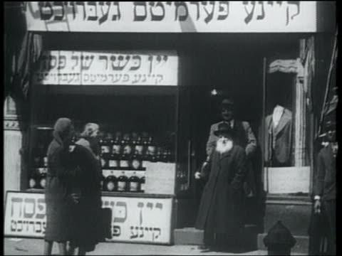 B/W 1932 men leaving Kosher wine store as women pass on sidewalk / Lower East Side, NYC
