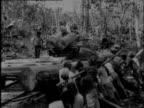 Men lift a heavy tree trunk on a track