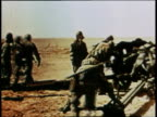 Men load and prepare to fire cannon / squad advances over desert in gas masks