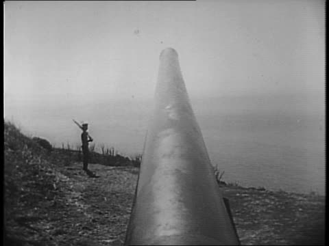 Men loading 16 inch artillery guns in interior chamber / men get shells into position load it into gun / packages of powder loaded behind the shell /...