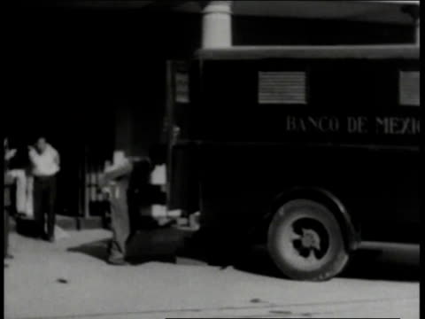Men loading bags of silver into bank truck / Mexico