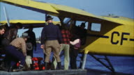 MS Men loading fire fighting equipment into yellow single engine double pontoon piper cub seaplane