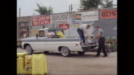 WS Men loading gardening equipment in 1961 Chevrolet corvair pick up truck / United States