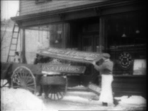 B/W 1920 men loading 'Wine Liquors' sign onto cart on city street / Prohibition / newsreel